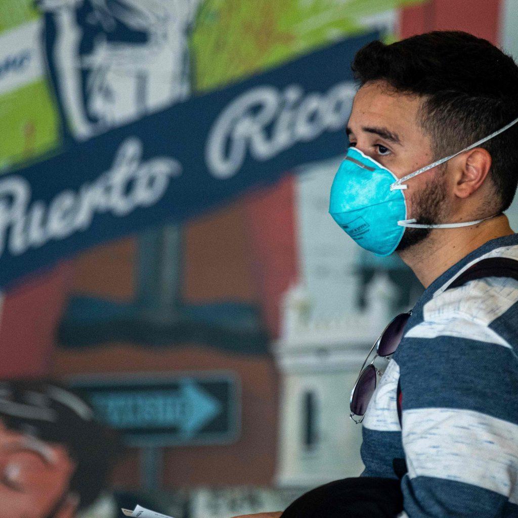 Viajere con mascara facial tras la pandemia del Coronavirus en el aeropuerto Luis Munos Marin en San Juan PR - ahora US